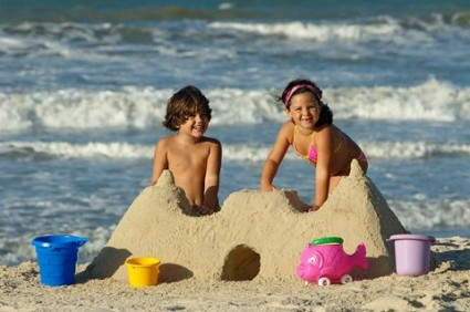 Crianças brincando na praia de castelo de areia